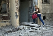 A woman rushes into her house destroyed in a shelling attack on Donetsk