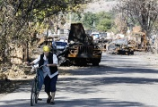 A local woman walks past destroyed military hardware in Ukraine's Luhansk Region