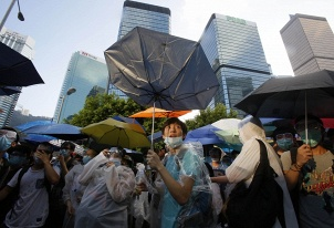 "The movement has been already labeled ""the Umbrella Revolution"" for the umbrellas that many people are holding to protect themselves from pepper spray and tear gas, as well as to cope with oppressive heat"